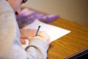 右手で字を書いている写真